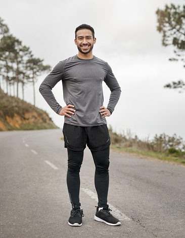 Full length portrait of a handsome young man standing alone after his run outdoors