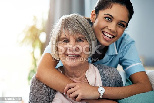 Portrait of a young nurse caring for a senior woman at home
