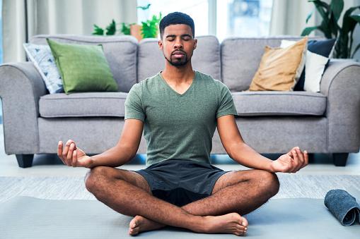 Shot of a young man meditating at home