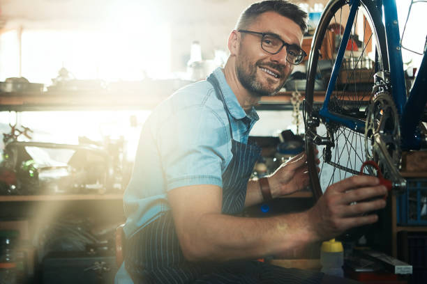 My repair work is backed by years of experience Portrait of a mature man working in a bicycle repair shop bicycle shop stock pictures, royalty-free photos & images