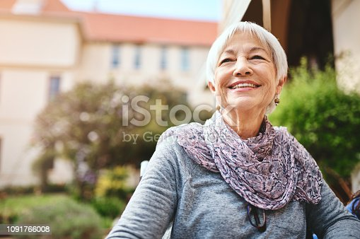 Shot of a senior woman relaxing outside in the garden of a retirement home