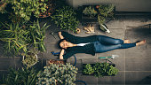 Young woman lying in her rooftop garden, having a rest from gardening