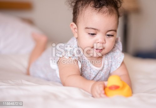 Shot of a beautiful baby girl lying on bed and playing with a toy duck