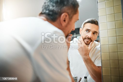 Shot of a mature man going through his morning routine in the bathroom at home