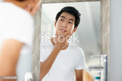 Shot of a handsome young man looking in a mirror in the bathroom at home
