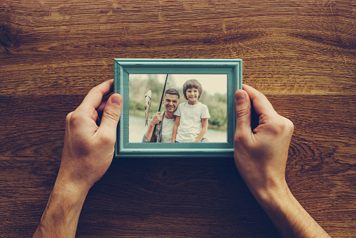Close-up top view of man holding photograph of himself and his son fishing over wooden desk