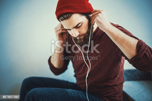 Closeup of early 20's bearded male student sitting in a hallway and taking a break by listening to his favorite song. He's dressed casually with a red beanie indoors.