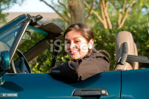Pretty young woman sitting in a sports car.