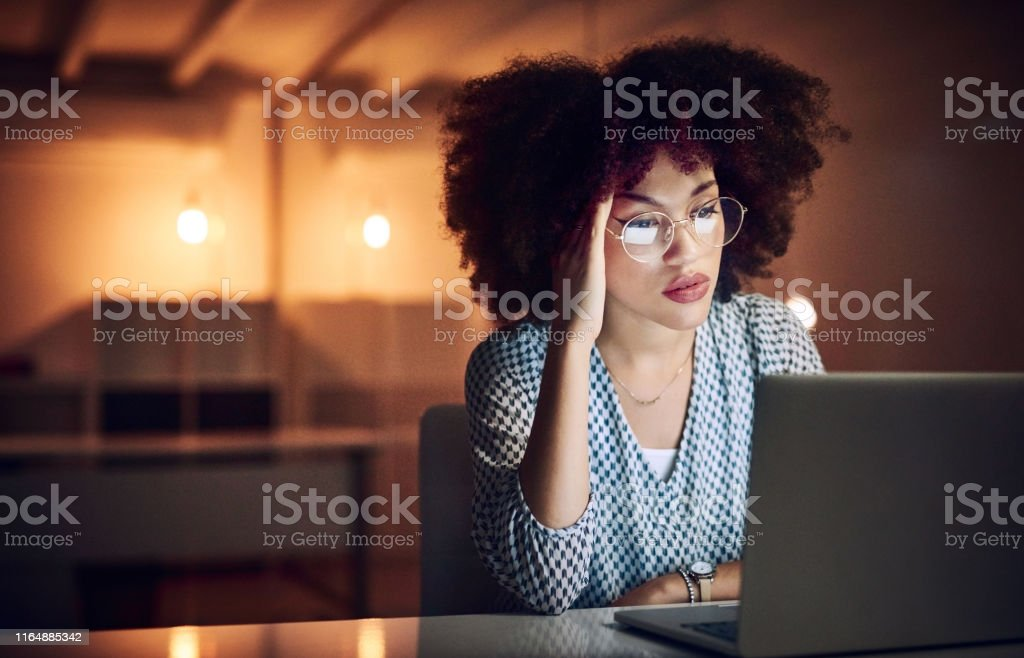My stress levels are increasing by the hour Shot of a beautiful young businesswoman looking stressed out while working late in her office 20-29 Years Stock Photo