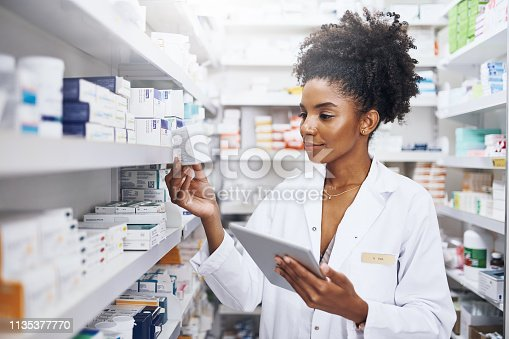 Cropped shot of a pharmacist using a digital tablet in a chemist