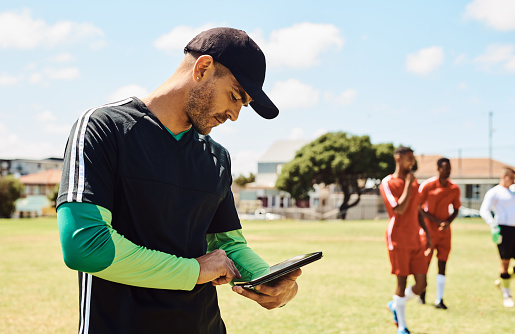 Shot of a soccer coach using a digital tablet while out on the field
