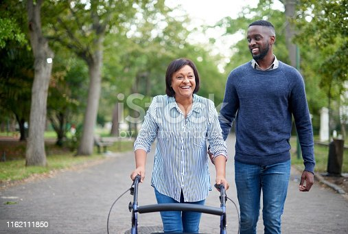 Cropped shot of a happy mature woman using a walker while a handsome young man assists her in the park