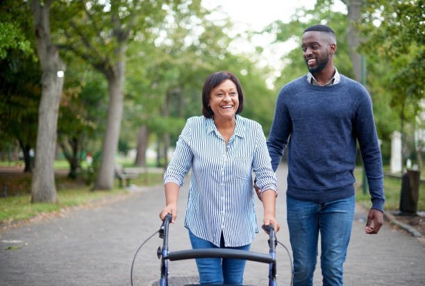 My therapist has helped me walk! Cropped shot of a happy mature woman using a walker while a handsome young man assists her in the park persons with disabilities stock pictures, royalty-free photos & images
