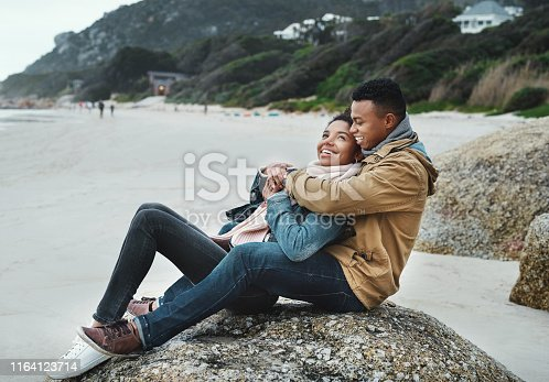 Shot of a young couple spending the day on the beach on a cloudy day