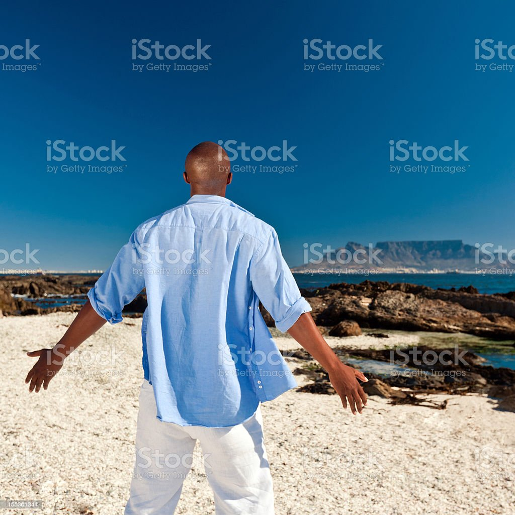 My world African man standing on the beach with arms wide open and looking at the horizon. Adult Stock Photo