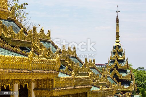 Architectural detail of the intricate gold ornamentation on the Chaukhtatgyi Buddha Temple in Yangon.