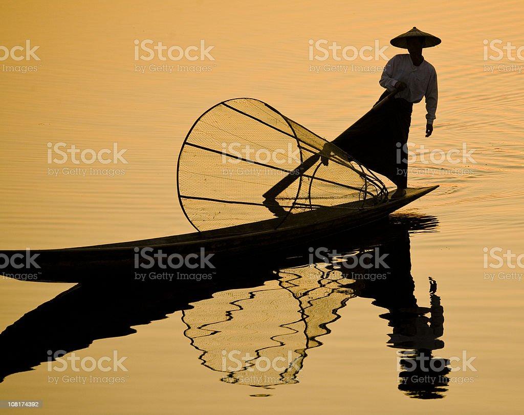 Myanmar: Leg-Rowing Fisherman on Inle Lake at Sunset royalty-free stock photo