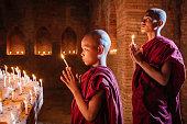 istock Myanmar Novice Monks Praying at Buddha Statue 1090757422