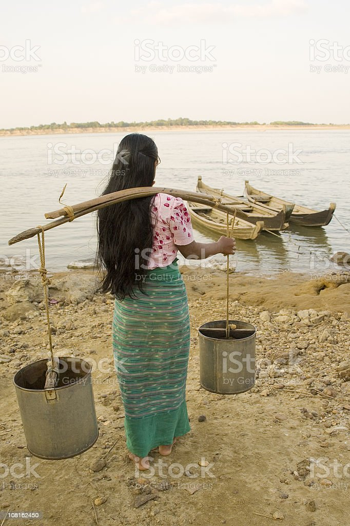 Myanmar Woman Carrying Water Cans to Rural River royalty-free stock photo