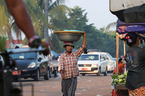 istock Myanmese woman with thanakha (Myanmar powder) on her face put big aluminum enameled basin on her head to bring the products to the market at Yangon. 1136780408