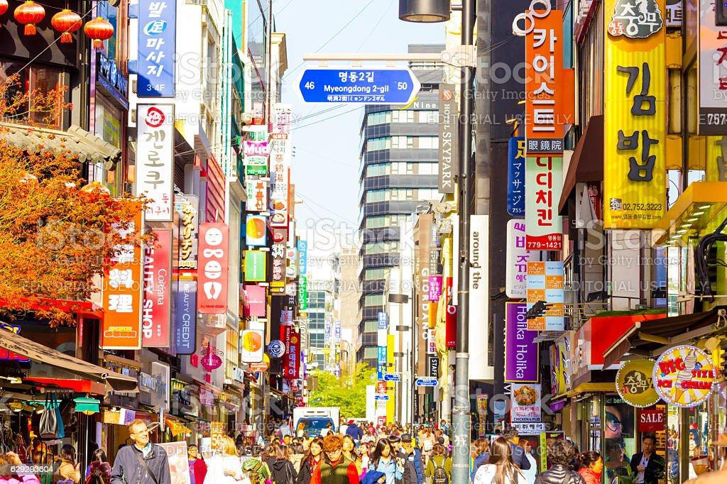 People walking down bustling Myeongdong pedestrian shopping street...