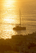 Sun sets over a yacht in Mykonos Harbour