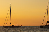 The sun sets over the Aegean Islands. A catamaran is in the background.