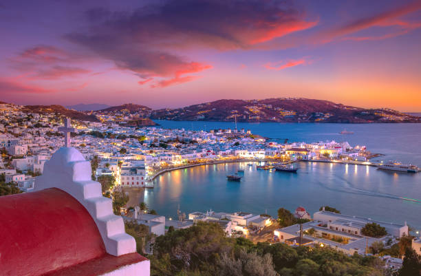 Mykonos port with boats and windmills at evening, Cyclades islands, Greece stock photo