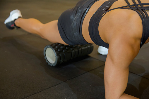 Shot of female athlete rolling her quad with foam roller at home, during Covid 19 outbreak