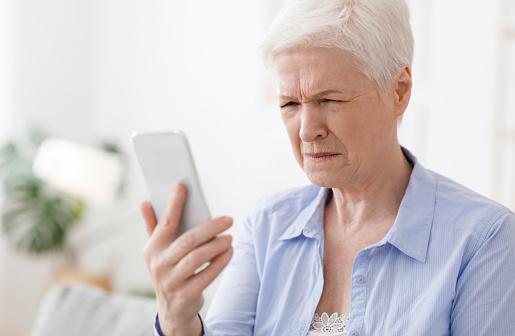 Myopia Concept. Elderly woman squinting while looking at smartphone screen, trying to read message, closeup