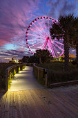 A view of the ferris wheel in Myrtle Beach from the boardwalk along the beach front.