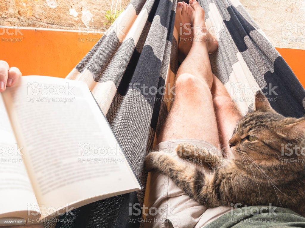 Mich, meine Katze und ein Buch auf einer Hängematte liegend – Foto