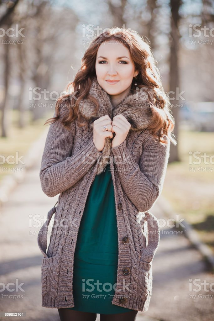 Mysterious adorable young brunette lady portrait with cute face and seducing lips professionally posing sit for camera wearing cosy warm designer clothes with fur in autumn spring central park stock photo