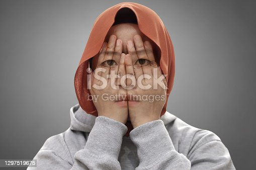 Mysterious Asian muslim covering her face with hands, multiple exposure shows her sad depressed facial expression
