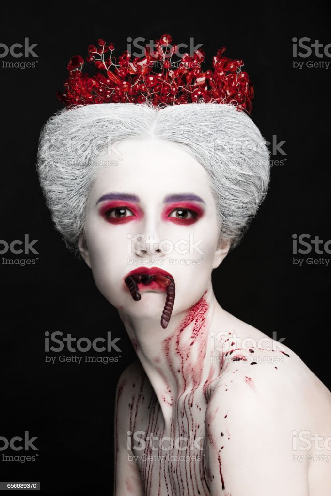 Mysterious beauty portrait of snow queen covered with blood. Bright luxury makeup. Jelly worms in the mouth. stock photo