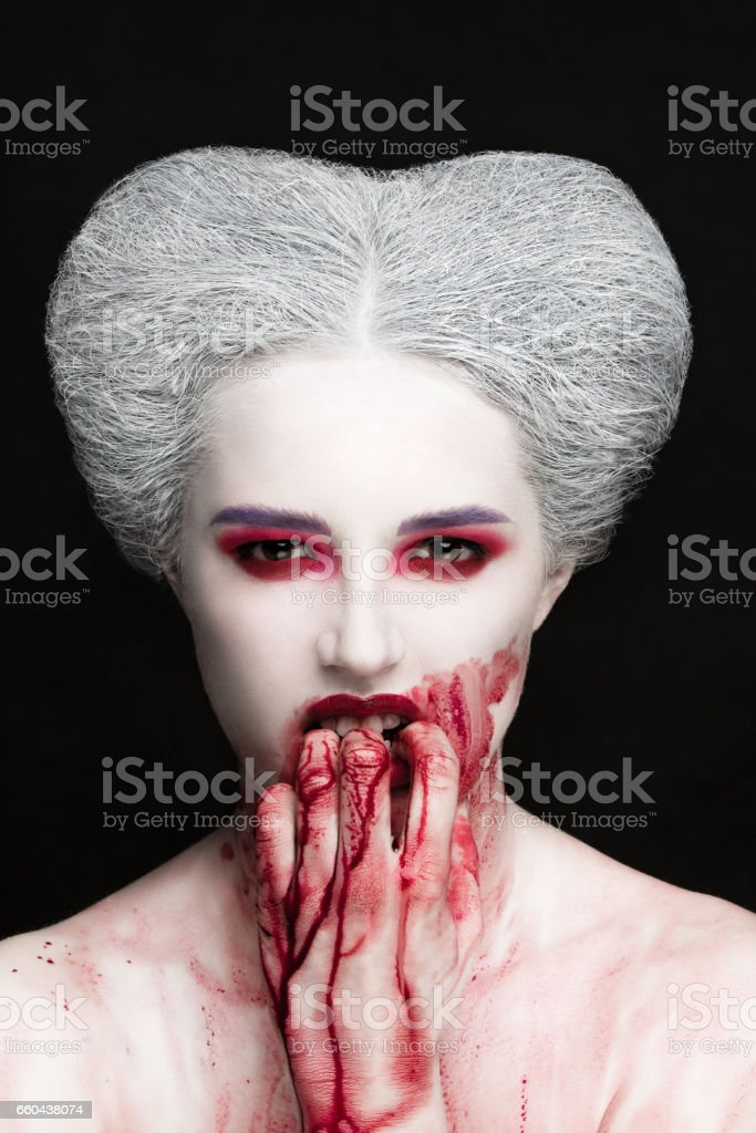 Mysterious beauty portrait of snow queen covered with blood. Bright luxury makeup. Gore dripping from the mouth. stock photo