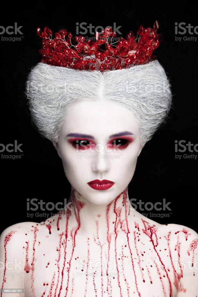 Mysterious beauty portrait of snow queen covered with blood. Bright luxury makeup. Black demon eyes. stock photo