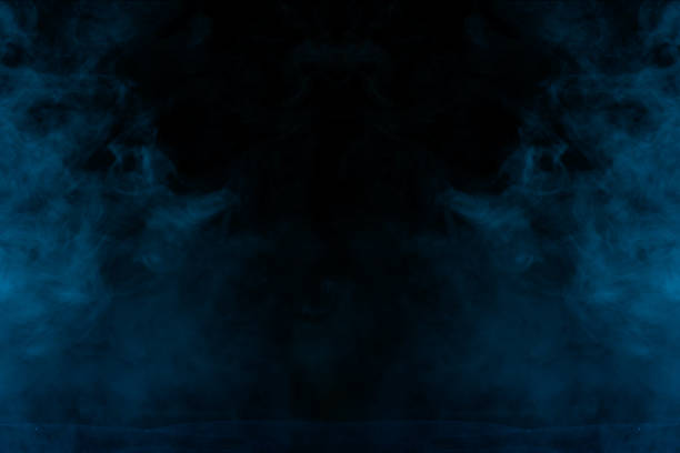 mysterious blue vapor on a dark background thick and transparent stock photo