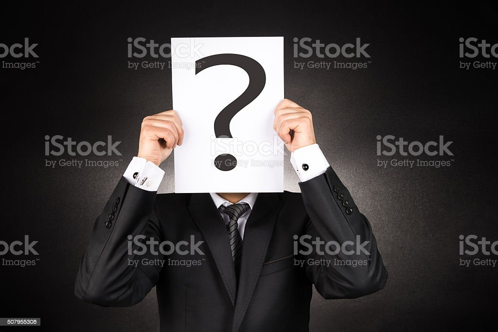 Mysterious Businessman holding question mark stock photo