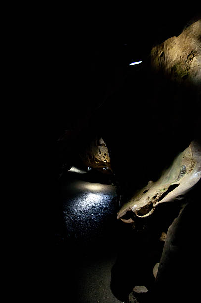 mysterious cavern spotlights on rocks in dark, dank, black limestone, dripstone cave arcane stock pictures, royalty-free photos & images