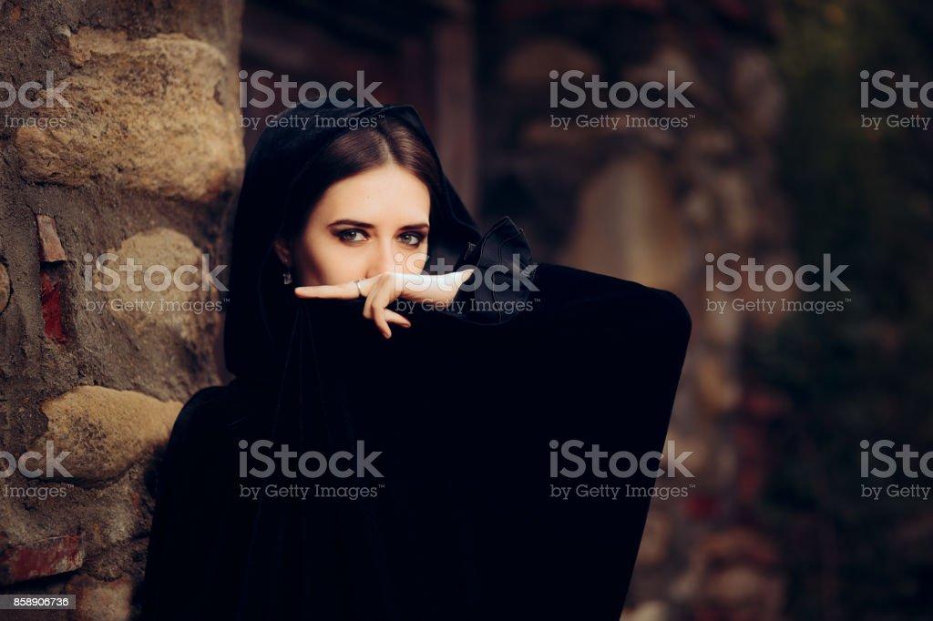 Bruja oscura misteriosa en capa negra con capucha - foto de stock