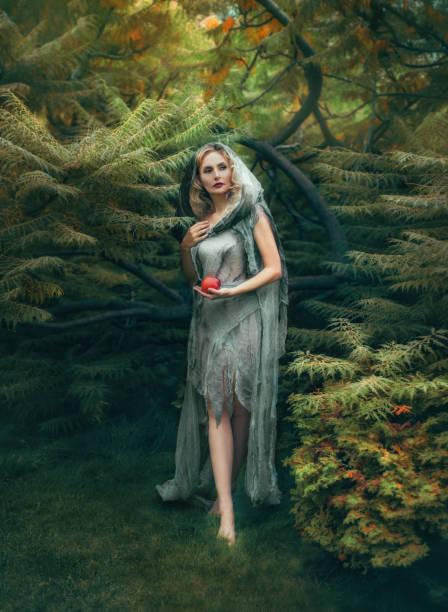 geheimnisvolle böse hexe mit blonden lockigen haaren kommt aus einem dichten wald mit ein roter apfel, in ein altes leinen kleid, das aussieht wie ein zerlumpten mantel mit kapuze. kunstfoto in warmen farben. halloween-kostüm - elfenkostüm damen stock-fotos und bilder