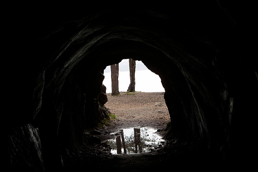 Mysterious Exit from a cave. Light at the end of the tunnel, visible tree trunks. Reflections in the water. Exploration concept. Cave corridor.