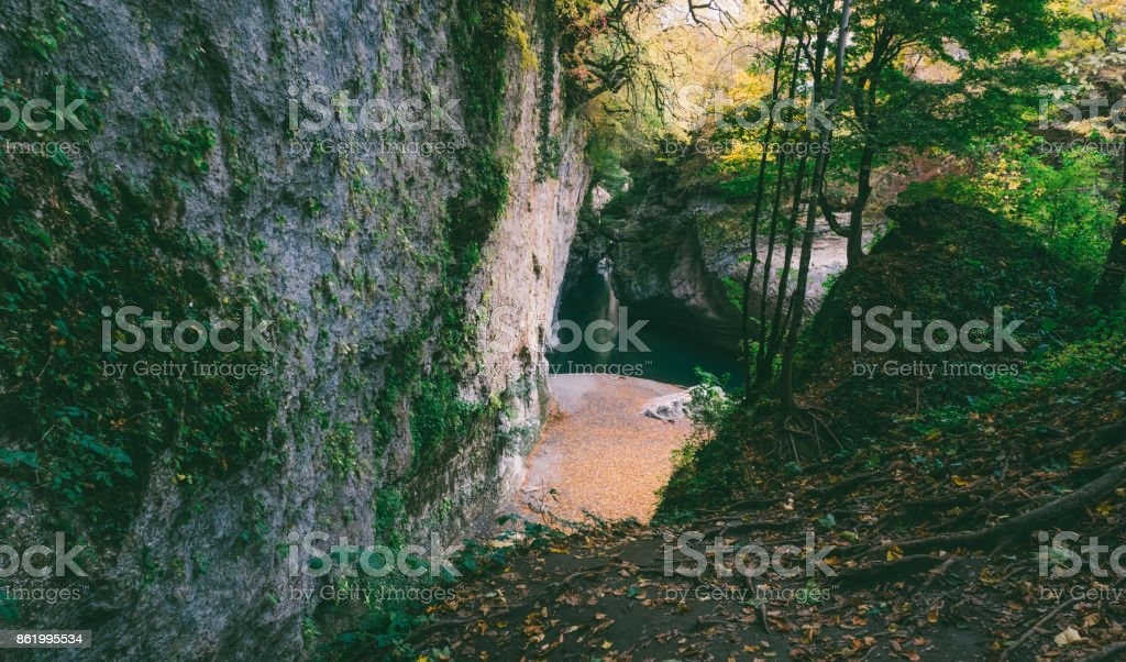 mysterious forest with cliffs and the river with bluish green water stock photo