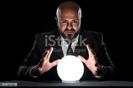 istock mysterious fortune teller gesturing at crystal ball 619772718