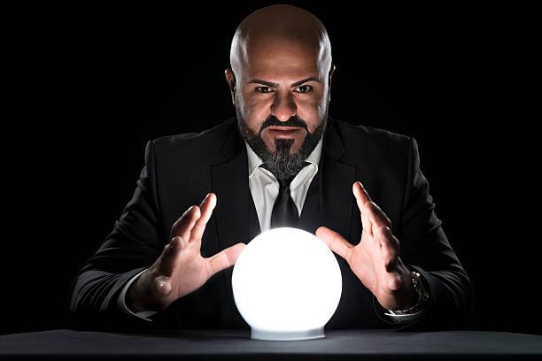 mysterious fortune teller gesturing at crystal ball - boule de cristal photos et images de collection