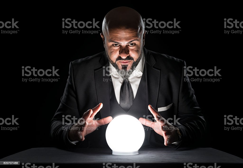 Mysterious Fortune Teller Gesturing At Crystal Ball Stock Photo