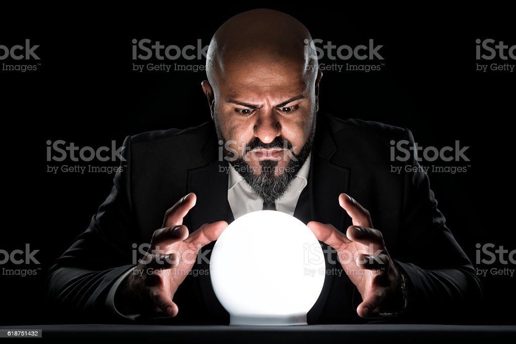 mysterious fortune teller looking at crystal ball stock photo