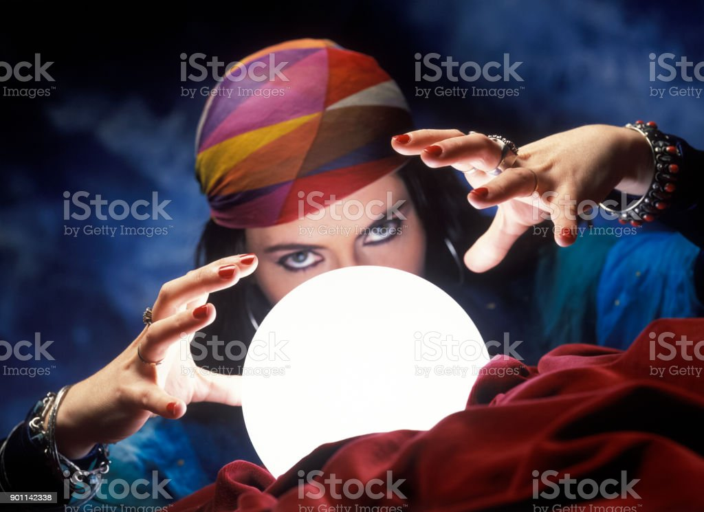 Mysterious fortune teller with  glowing crystal ball stock photo