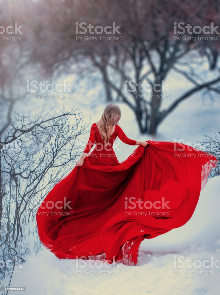 Mysterious girl runs, spinning in a red dress, with a very long train. Hair is flying in the wind. Photo without a face, from the back. Woman escapes from problems, gaining freedom. Background winter stock photo